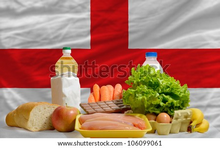 complete national flag of england covers whole frame, waved, crunched and very natural looking. In front plan are fundamental food ingredients for consumers, symbolizing consumerism