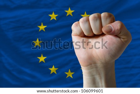 complete national flag of europe covers whole frame, waved, crunched and very natural looking. In front plan is clenched fist symbolizing determination - stock photo