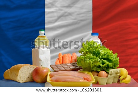 complete national flag of france covers whole frame, waved, crunched and very natural looking. In front plan are fundamental food ingredients for consumers, symbolizing consumerism - stock photo