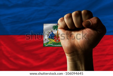 complete national flag of haiti covers whole frame, waved, crunched and very natural looking. In front plan is clenched fist symbolizing determination - stock photo