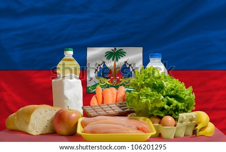 complete national flag of haiti covers whole frame, waved, crunched and very natural looking. In front plan are fundamental food ingredients for consumers, symbolizing consumerism - stock photo