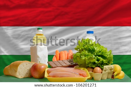 complete national flag of hungary covers whole frame, waved, crunched and very natural looking. In front plan are fundamental food ingredients for consumers, symbolizing consumerism - stock photo