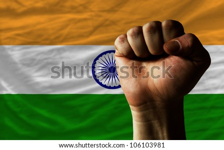 complete national flag of india covers whole frame, waved, crunched and very natural looking. In front plan is clenched fist symbolizing determination - stock photo