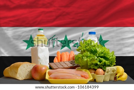 complete national flag of iraq covers whole frame, waved, crunched and very natural looking. In front plan are fundamental food ingredients for consumers, symbolizing consumerism - stock photo