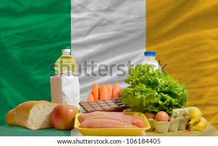 complete national flag of ireland covers whole frame, waved, crunched and very natural looking. In front plan are fundamental food ingredients for consumers, symbolizing consumerism - stock photo