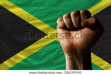 complete national flag of jamaica covers whole frame, waved, crunched and very natural looking. In front plan is clenched fist symbolizing determination - stock photo