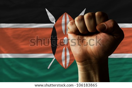 complete national flag of kenya covers whole frame, waved, crunched and very natural looking. In front plan is clenched fist symbolizing determination - stock photo
