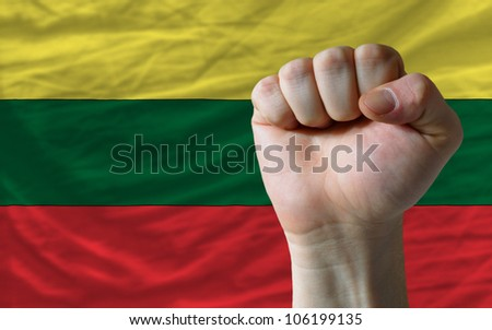 complete national flag of lithuania covers whole frame, waved, crunched and very natural looking. In front plan is clenched fist symbolizing determination - stock photo