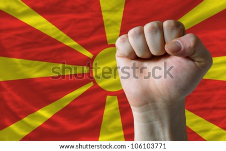 complete national flag of macedonia covers whole frame, waved, crunched and very natural looking. In front plan is clenched fist symbolizing determination - stock photo