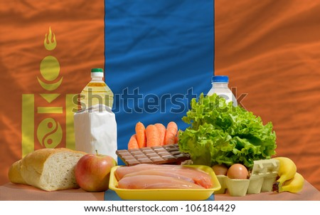 complete national flag of mongolia covers whole frame, waved, crunched and very natural looking. In front plan are fundamental food ingredients for consumers, symbolizing consumerism - stock photo