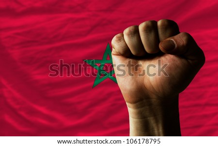complete national flag of morocco covers whole frame, waved, crunched and very natural looking. In front plan is clenched fist symbolizing determination - stock photo