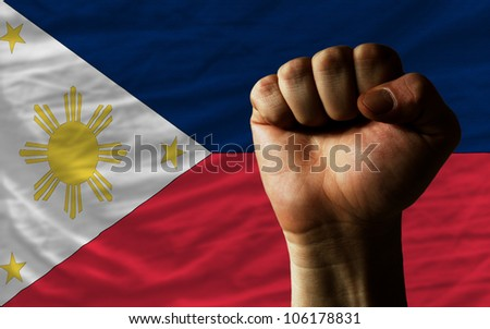 complete national flag of philippines covers whole frame, waved, crunched and very natural looking. In front plan is clenched fist symbolizing determination - stock photo
