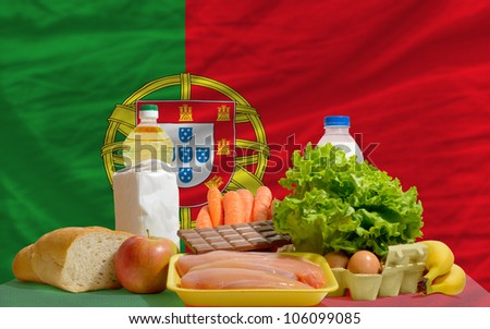 complete national flag of portugal covers whole frame, waved, crunched and very natural looking. In front plan are fundamental food ingredients for consumers, symbolizing consumerism - stock photo