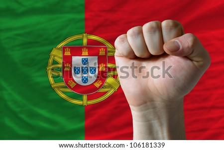 complete national flag of portugal covers whole frame, waved, crunched and very natural looking. In front plan is clenched fist symbolizing determination - stock photo