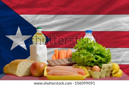 complete national flag of puerto rico covers whole frame, waved, crunched and very natural looking. In front plan are fundamental food ingredients for consumers, symbolizing consumerism an human needs - stock photo