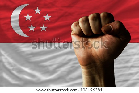 complete national flag of singapore covers whole frame, waved, crunched and very natural looking. In front plan is clenched fist symbolizing determination - stock photo
