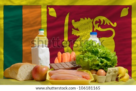 complete national flag of srilanka covers whole frame, waved, crunched and very natural looking. In front plan are fundamental food ingredients for consumers, symbolizing consumerism - stock photo