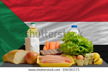 complete national flag of sudan covers whole frame, waved, crunched and very natural looking. In front plan are fundamental food ingredients for consumers, symbolizing consumerism - stock photo