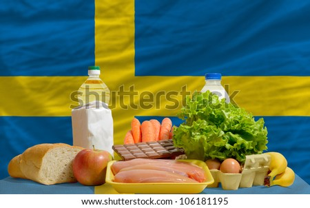complete national flag of sweden covers whole frame, waved, crunched and very natural looking. In front plan are fundamental food ingredients for consumers, symbolizing consumerism - stock photo