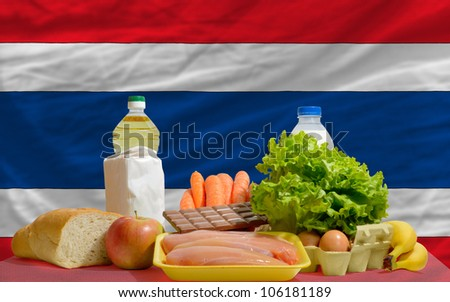 complete national flag of thailand covers whole frame, waved, crunched and very natural looking. In front plan are fundamental food ingredients for consumers, symbolizing consumerism - stock photo