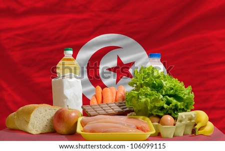 complete national flag of tunisia covers whole frame, waved, crunched and very natural looking. In front plan are fundamental food ingredients for consumers, symbolizing consumerism an human needs - stock photo