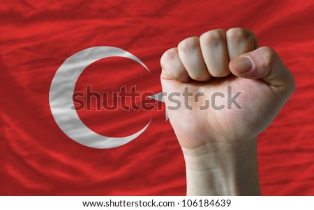 complete national flag of turkey covers whole frame, waved, crunched and very natural looking. In front plan is clenched fist symbolizing determination - stock photo