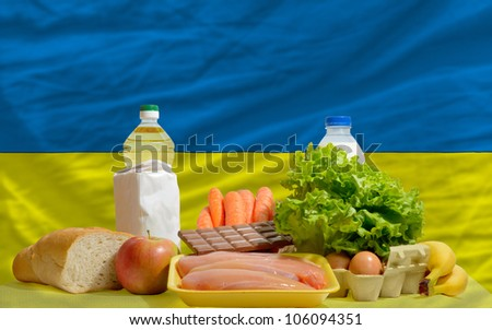 complete national flag of ukraine covers whole frame, waved, crunched and very natural looking. In front plan are fundamental food ingredients for consumers, symbolizing consumerism an human needs - stock photo