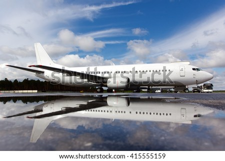 Completely white passenger plane. Aircraft is parked at the airport field and is reflected in a puddle.