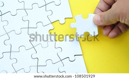 Completing a jigsaw puzzle - stock photo