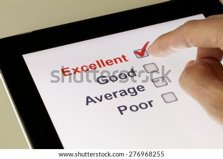Completing online survey on a tablet, clicking excellent - stock photo