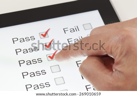 Completing the form on a digital tablet, clicking all pass - stock photo