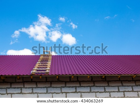 completion of construction of the house. two wooden ladders are on both sides of the iron roof. beautiful blue sky with clouds. copy space for your text - stock photo
