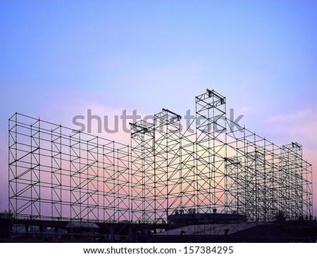 Complex scaffolding setup for a stage for an outdoor concert seen at sunset - stock photo