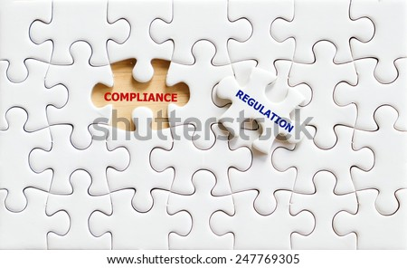 Compliance and Regulation words written on white puzzle piece,business concept background - stock photo