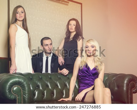 Complicated love relationship. Party in a closed club. One man and three women. The man next to the women in the room. Love triangle. The concept of modern bachelor lifestyle. Love story four people. - stock photo