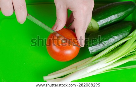 components for salad: tomatoes, a cucumber, green onions, on a green chopping board
