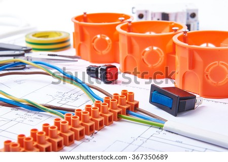 Components for use in electrical installations. Connectors, junction box, switch, isolation tape and wires. Accessories for engineering work, energy concept. - stock photo
