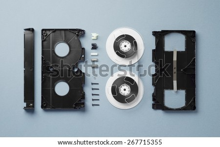 Components of a VHS Cassette disassembled and well arranged over blue background - stock photo
