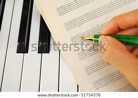 Composing music and writing on old music score on a black and white piano keyboard. For concepts like music and creativity. - stock photo