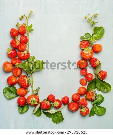 Composing of strawberries with green leaves and flowers on wooden background, top view, place for text - stock photo