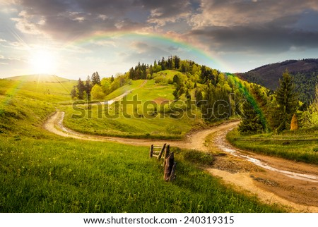 composite autumn landscape. fence near the cross road on hillside meadow in mountains. few fir trees of forest  on both sides of the road in sunset light with rainbow - stock photo