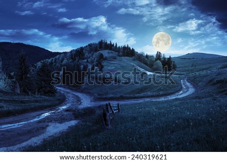 composite autumn landscape. fence near the cross road on hillside meadow in mountains. few fir trees of forest  on both sides of the road at night in full moon light - stock photo