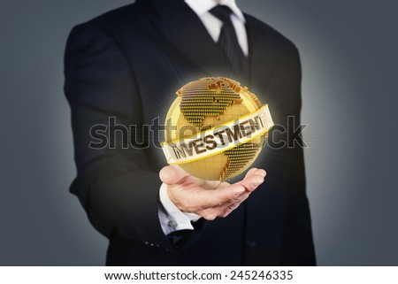 Composite image of a businessman holding a golden globe with investment text - stock photo