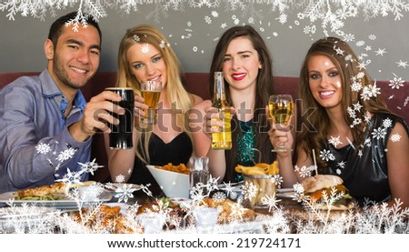 Composite image of a Friends having dinner together smiling at camera against frost - stock photo