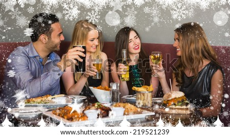 Composite image of a Happy friends sitting together having dinner against snow - stock photo
