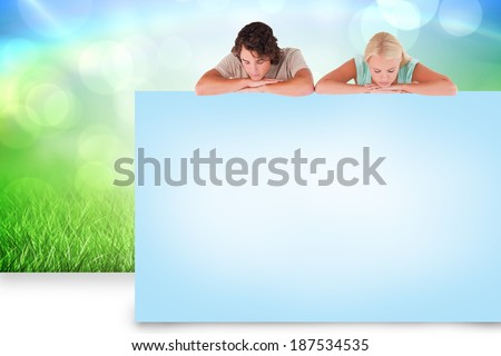 Composite image of attractive couple showing blue card