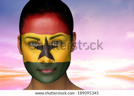 Composite image of beautiful brunette in ghana facepaint against beautiful blue and yellow sky - stock photo