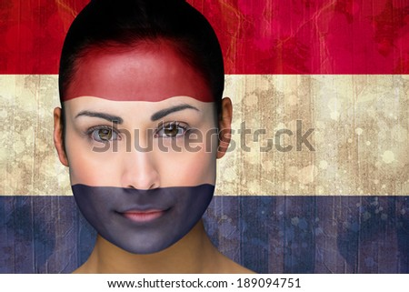 Composite image of beautiful football fan in face paint against netherlands flag in grunge effect