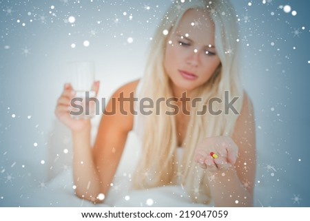 Composite image of blonde woman looking at a pill against snow - stock photo