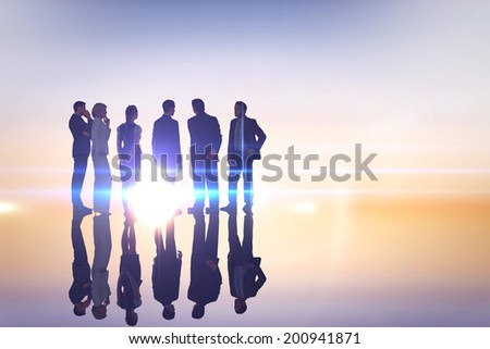 Composite image of business colleagues standing against purple and orange sky - stock photo